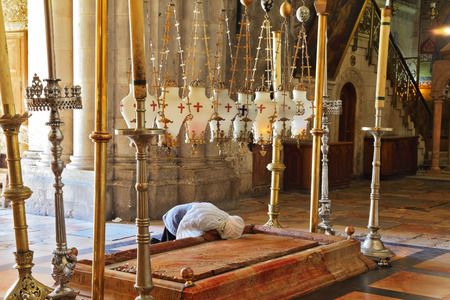 Church of the Holy Sepulcher in Jerusalem. Pilgrim prays in a white veil over the Stone of Unction Editorial