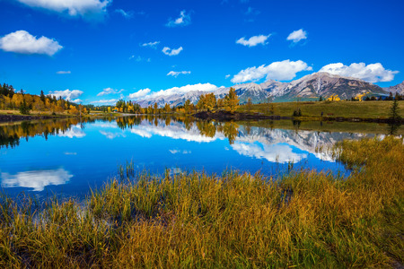 canmore: The concept of hiking. Bright shining autumn day in Canmore, near Banff National Park. Majestic mountains and scenic cumulus clouds are reflected in the lake