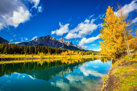 canmore: The concept of recreational tourism. Canmore, near Banff National Park. Jagged mountains and red-orange trees are reflected in smooth water of the lake Stock Photo