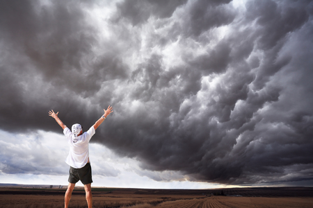 thundercloud: The elderly man in delight from an enormous thundercloud over fields of Montana