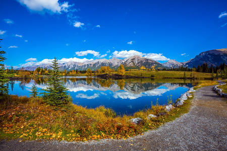canmore: Path around the lake. The concept of hiking. Canmore, near Banff National Park. Majestic mountains and scenic cumulus clouds are reflected in the water Stock Photo