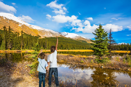 Two boys stand on the coast of the marshy lake. The concept of active tourism. Rocky Mountains on a sunny day