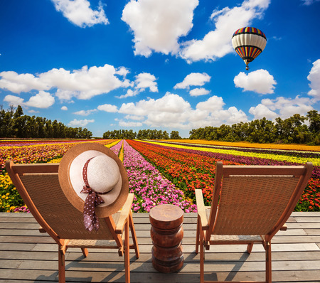 ecological tourism: Concept of ecological tourism. Rural rest. Wooden chaise lounges  in the meadow with flowers.  Huge balloon flies over the field Foto de archivo