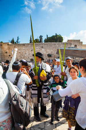 talmud: JERUSALEM, ISRAEL - OCTOBER 12, 2014:  Morning autumn Sukkot. The area in front of Western Wall of Temple filled with people. The Jews of ritual clothes - tallit hold four plants on Sukkot Stock Photo