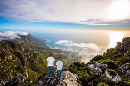 table mountain national park: The concept of active tourism and recreation. Two boys standing on top of Table Mountain in the clouds. Travel to Africa