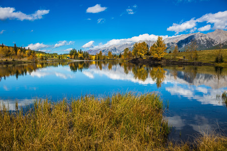 canmore: Canmore, near Banff. Concept hiking. Blue sky and clouds reflected in smooth water of the lake. Shining day in the Canadian Rockies