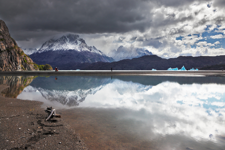 Iceberg in the lake. Bright reflections of sky and clouds in the smooth cold water of Lake Grey. Chilean Patagonia, National Park Torres del Paine