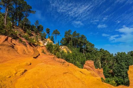 Unieke rode en oranje heuvels in de provincie Roussillon, Frankrijk. Naaldwouden vormen een mooi contrast met de kleur van oker Stockfoto
