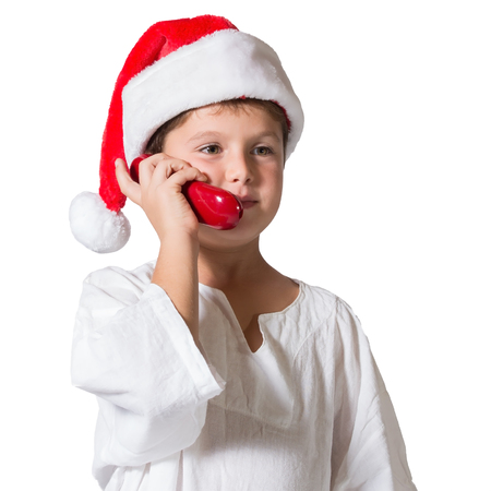 Very beautiful seven year old boy in a red cap. He is talking on the red phone Stock Photo