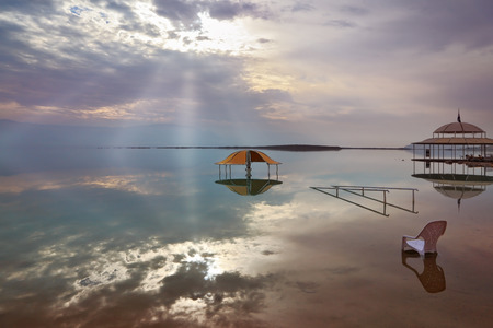 visual effect: A stunning visual effect on the Dead Sea. The picturesque gazebo for bathers and sun rays are reflected in a smooth sea surface.