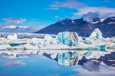 Ice lagoon in Iceland. Ocean Bay is surrounded by volcanic mountains and glaciers. Icebergs and ice floes are reflected in the mirrored water Stock Photo
