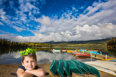 Very beautiful seven year old boy in a carnival wearing a crown of shiny green leaves. He sits astride a chair Wooden boat dock with moored pleasure boats and benches. Fluffy cumulus clouds over the Pyramid mountain and Pyramid Lake