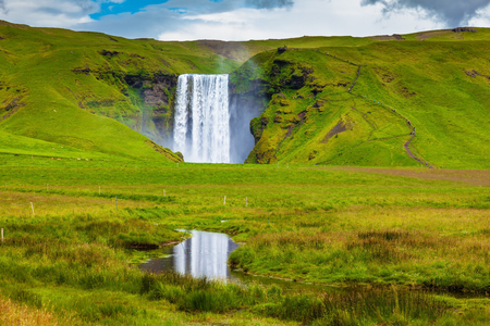 Grandiose reflection. The huge deep falls Skogafoss are reflected in small stream Stock Photo