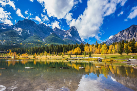 canmore: Shallow lakes surrounded by forests and mountains. Shining day in Canmore, Canadian Rockies. Concept of hiking Stock Photo