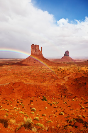 Certain rocks - mitts are crossed with a picturesque rainbow. Red stone desert of an Indian tribe of the Navajo, USA