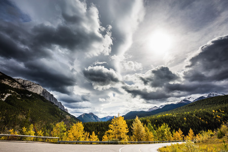sharply: The road bends sharply in the woods. Perfect storm sunset over the Rocky Mountains