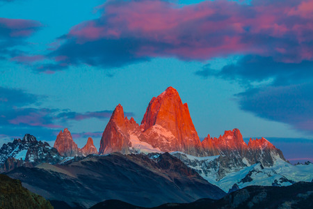 Amazing Patagonia in February. Sharp tops fantastically beautiful cliffs Fitz Roy crimson light rays of sunset Stock Photo
