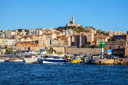On the hill - splendid Basilica of Notre-Dame de la Garde in Marseille. The water area of the Old Port - yachts, speedboats and fishing boats
