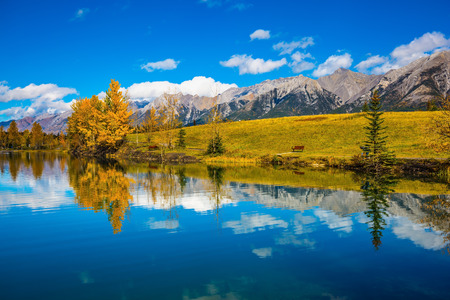 The concept of recreational tourism. Bright shining autumn day in Canmore, near Banff National Park. Scenic cumulus clouds are reflected in the lake 스톡 콘텐츠