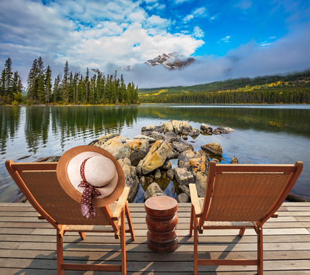 Concept of  vacation and tourism. Two deck chairs on a wooden platform. On the chair hangs an elegant straw hat. Pyramid Lake, Jasper National Park