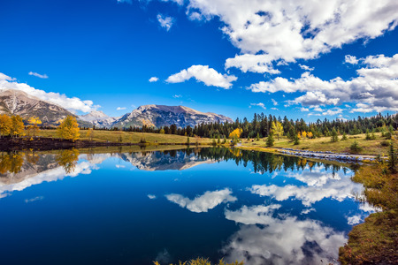 canmore: The concept of recreational tourism. Bright shining autumn day in Canmore, near Banff National Park. Majestic mountains and scenic cumulus clouds are reflected in the lake Stock Photo