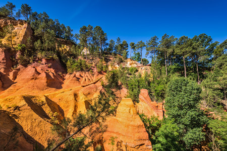 ochre:  Multi-colored ocher outcrops - from yellow to orange-red. Green trees create contrast with the ocher. Roussillon, Provence Red Village Stock Photo