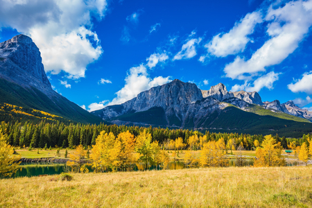 canmore: Concept of trekking.  The Three Sisters mountains in Canadian Rockies. Shining sunny day in Canmore. Mountain peaks and white clouds
