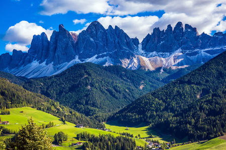 Odle mountain peaks surround the green alpine meadows of the valley. Dolomites, Val de Funes valley. Lovely sunny day in  Nature Park Puez-Odle