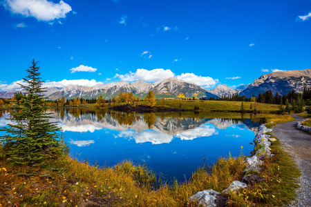 canmore: Path around the lake. Canmore, near Banff National Park. Majestic mountains and scenic cumulus clouds are reflected in the water. The concept of recreational tourism Stock Photo