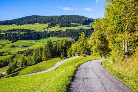 turismo ecologico: Las montañas boscosas rodeadas de prados alpinos verdes. El camino desciende en el Val de Funes. Otoño en las dolomías. El concepto de turismo ecológico