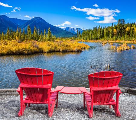 turismo ecologico: Dos salones chaise convenientes rojas en la orilla del lago. Concepto de turismo ecológico. verano indio en las Montañas Rocosas de Canadá