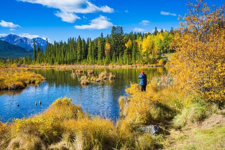 turismo ecologico: La mujer - turística en una chaqueta de fotografías una multa paisaje. Concepto de turismo ecológico. verano indio en las Montañas Rocosas de Canadá
