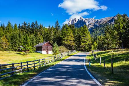 turismo ecologico: La carretera de asfalto desciende en el Val de Funes. otoño caliente en los Dolomitas. picos rocosos y montañas boscosas rodeada de prados alpinos verdes. El concepto de turismo ecológico
