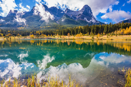 canmore: The concept of recreational tourism. Bright shining day in the Canadian Rockies. Canmore, near Banff National Park. Majestic mountains and red-orange trees Stock Photo
