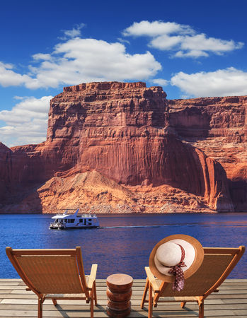 At the stern of the boat are two deck chairs. On the back of one hanging elegant ladies straw hat. Walk to the tourist boat on Lake Powell on the Colorado River