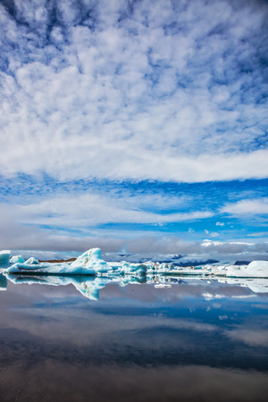 mirror on the water: Iceland. Ice magnificence. Floating ice and clouds are reflected in smooth mirror water of the Ice lagoon Stock Photo