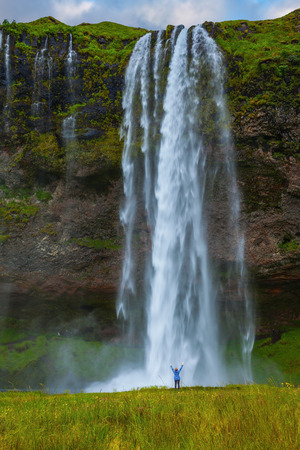 The warm July day in Iceland. Seljalandsfoss waterfall. Enthusiastic middle-aged woman admires the beauty and power of the falls Stock Photo