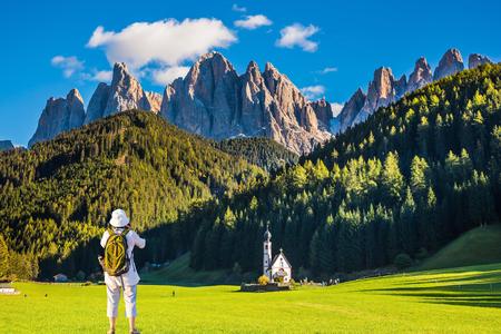turismo ecologico: Dolomitas, Tirol. Mujer activa-turística con mochila fotografía la iglesia de Santa Magdalena. montañas boscosas rodeada de prados alpinos verdes. El concepto de turismo ecológico y activo Foto de archivo