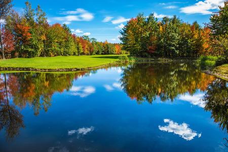 Bromont, 프랑스 캐나다에 도로에 골프 클럽. 환상적인 아름다움의 공원. 골프 관광의 개념입니다. 빨강, 오렌지 및 녹색 단풍이 호수의 맑은 물에 반영됩