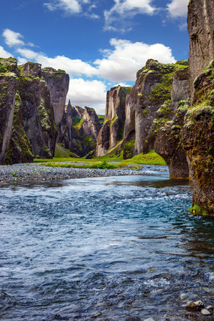 legends: Canyon Icelandic fairy tales and legends - Fyadrarglyufur. Steep cliffs, overgrown with green moss, surrounded by a very fast river with cold water