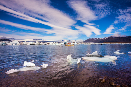 The clouds and ice floes of lagoon Jokulsarlon, Iceland. Clouds cirrocumulus reflected in the water of lagoon. The concept of northern extreme tourism Stock Photo