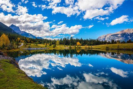 canmore: Blue sky and clouds reflected in smooth water of the lake. Shining day in the Canadian Rockies. Canmore, near Banff. Concept hiking