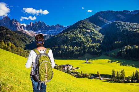 turismo ecologico: Mayor activa de la mujer-turística con mochila admirar el paisaje. Día soleado en dolomías. montañas boscosas rodeada de prados alpinos verdes. El concepto de turismo activo y ecológico