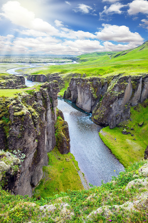 Northern sun shines over the tundra. Bizarre shape of cliffs surround the stream with glacial water. The Icelandic Tundra in July