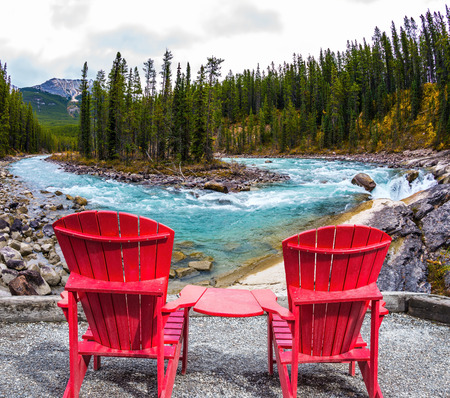 turismo ecologico: Two red deckchairs stand on the shore of the waterfall. Canada. Small island in the middle of the river. The concept of extreme and ecological tourism