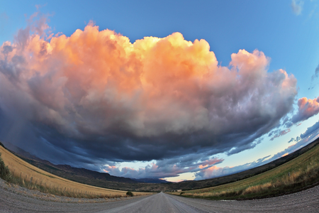 Huge pink - orange cloud, like a bowl of cream, lit the last rays of sunset. Gravel road through the Patagonian steppe. Picture taken Fisheye lens