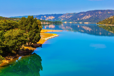 Smooth emerald green water of Lake Sainte-Croix-du-Verdon reflects the sky and wooded shore. Mountain canyon Verdon in the French Alps Stock Photo