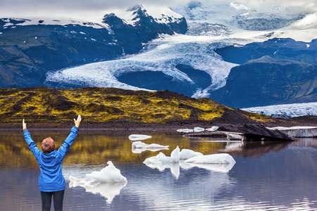 The elderly woman in a blue jacket, admiring the ice in the lagoon. The concept of extreme northern tourism. Ice floes are reflected in the smooth water surface of Ice Lagoon