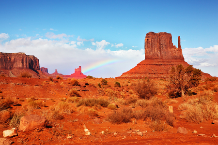 Famous rock - mitts of red sandstone. In the sky a rainbow. Magical landscape Monument Valley in Arizona