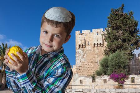 Charming seven year old boy in white festive skullcap with etrog. Sukkot in Jerusalem